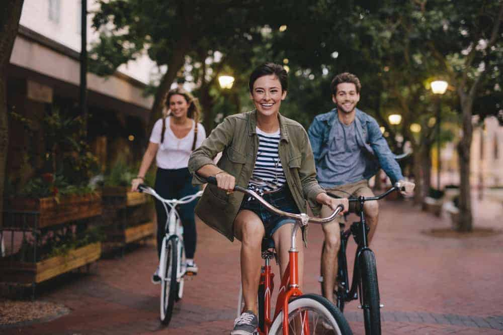 Friends riding bikes down sidewalk in Bountiful, UT