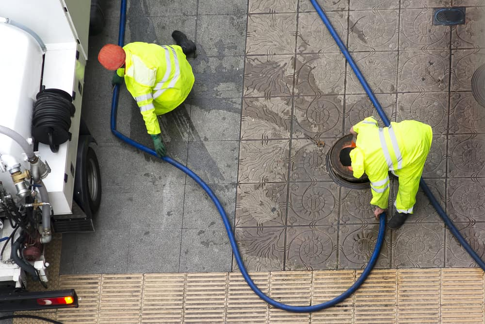 Water company workers arranging hoses