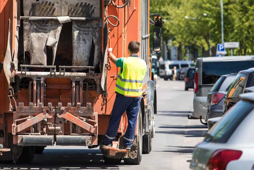 Garbage men picking up driving garbage truck
